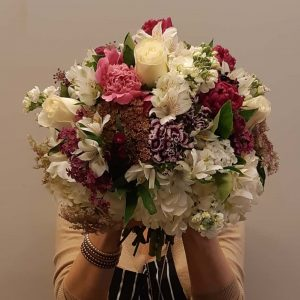 woman holding a bouquet of different flowers